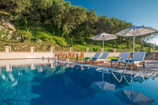 Gallery Corfu Hotel Philoxenia the Swimming Pool are has many sunbeds, chairs, umbrellas with view of the Ionian Sea and the Mountain